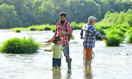 Fly fishing. Senior man fishing with son and grandson. Male multi generation family. Family generation and people concept. 写真素材