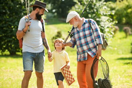 Summer weekend. Happy grandfather, father and grandson with fishing rods. Anglers. Men day. Fishing.