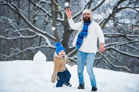 Winter game for happy family. Christmas Celebration holiday. Father and son play with snowball on winter white background.