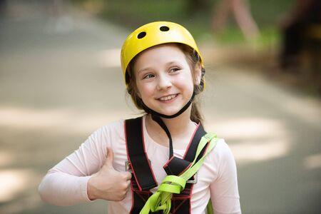 Helmet - safety equipment for Little girl playing. Helmet and safety equipment. Rope park - climbing center. Children fun Hiking in the rope park girl in safety equipment. Roping park.