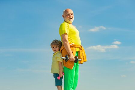 Old mature man and little boy exercising with dumbbell. Family sport. Healthy family lifestyle. Father and children having workout.