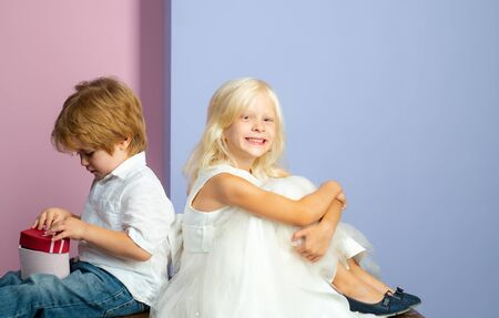 Melt her heart with gift. Friendship and love. Lovely tender children. Small kids friendship. Sincere friendship. Couple adorable kids white clothes. Happy childhood. Boy and girl cute friends Stockfoto