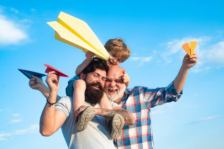 Happy three generations of men have fun and smiling on blue sky background. Enjoy family together. Dream of flying. Kids playing with simple paper planes on sunny day.