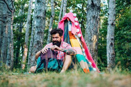 Gemütliches Spielzelt für den Mann im Waldpark. Wander- und Erholungskonzept im Freien mit flachen Campingreisen. Schöner bärtiger Mann, der sich im Abenteuerpark amüsiert.