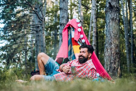 Cozy play tent for man on nature over sky background - isolated. Handsome bearded man having fun in adventure Park.