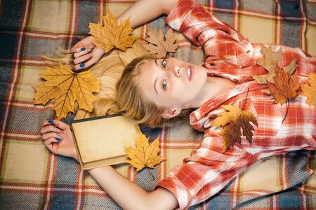 Beautiful sensual blonde playing with leaves. Fashion portrait of beautiful sensual woman. Girl wearing in autumn clothes on autumn sunny day. Beautiful girl with background board for Copyspace. Stockfoto