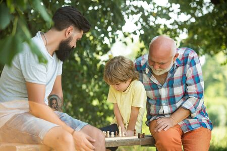 Happy loving family. Grandfather and grandson are playing chess and smiling while spending time together in park. Fathers day. 写真素材