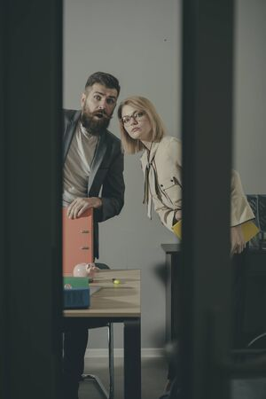 Business man and sexy woman look out with surprised faces. Business couple with binders in modern office with glass walls