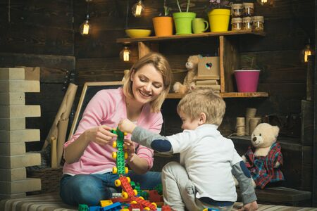 Playroom concept. Playroom is where imagination go wild. Mother and child play with toy bricks in playroom. Mother and son build structure model in playroom Reklamní fotografie