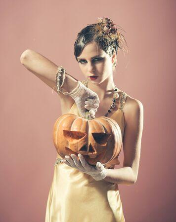 halloween Girl in yellow dress with pumpkin.