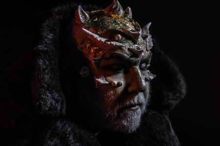 Severe king of perpetual cold kingdom wearing black fur coat. Magical creature with horns on head and golden dragon skin, supernatural concept. Demon head with thorns on face over dark background