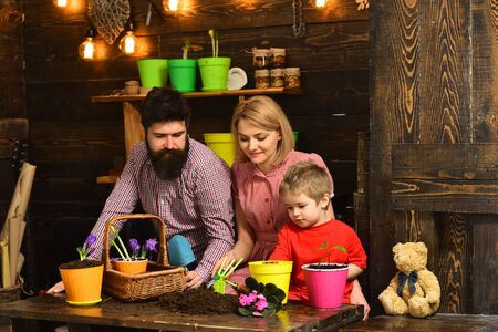 Earth day concept. Family replant flower in new pot on Earth day. Child boy with mother and father potting flower on Earth holiday. Make every day Earth day Reklamní fotografie