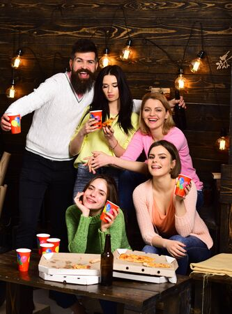 Youth celebrate with drinks and pizza, spend time together, speaking. Students, friends, group mates with teacher celebrate, have fun, dark wooden interior background. Students pizza party concept