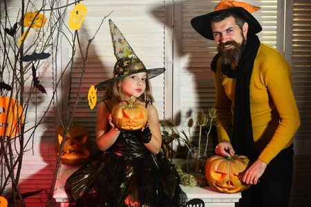 Halloween party concept. Wizard and little witch in hats