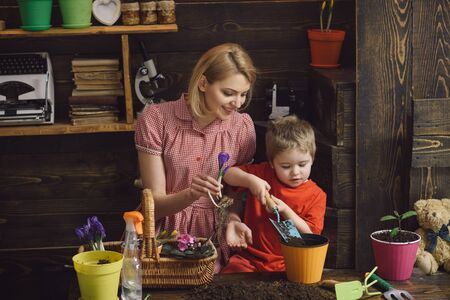 Flower concept. Mother and little son plant flower in pot. Flower shop. Every flower is a soul blossoming in nature