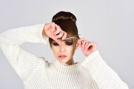 Beautiful brunette about to cut hair, studio. Stock fotó
