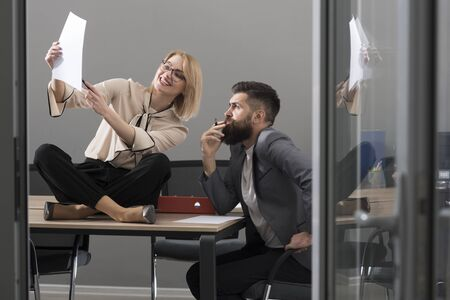 Businesswoman and businessman write business plan. Collaboration for success. Busy day in office. Sensual woman and bearded man work together in office. Concentrated on work
