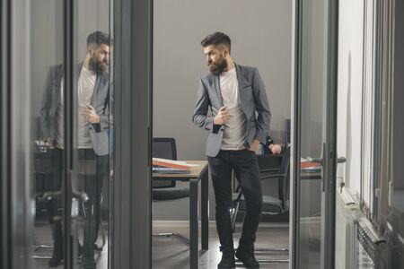Business man look out office door. Business man in modern office with glass walls Stock fotó