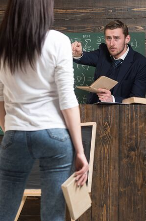Answer my question. Teacher and girl student rear view. Man teach woman in classroom. Education in university or home schooling. Examination or lesson. Back to school