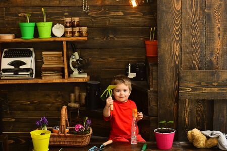 Child concept. Little child with gardening tools. Cute child in garden shed. Happy child gardener Фото со стока