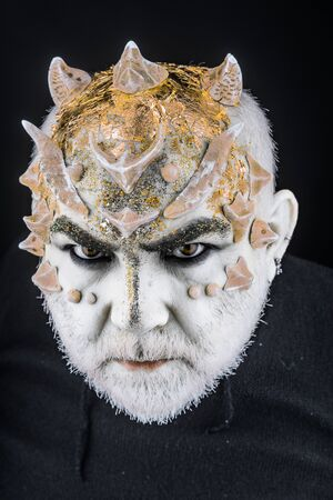 Head with thorns or warts, face covered with glitters, close up. Alien, demon, sorcerer makeup. Fantasy concept. Demon on serious face, black background. Senior man with beard, with monster makeup.