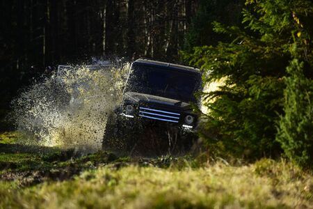 Rallying, competition and four wheel drive concept. Motor racing in autumn forest. Sport utility vehicle or SUV crossing puddle with splash. Offroad race on fall nature background. Stockfoto