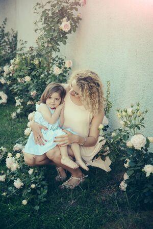 Mom cuddling daughter on green grass