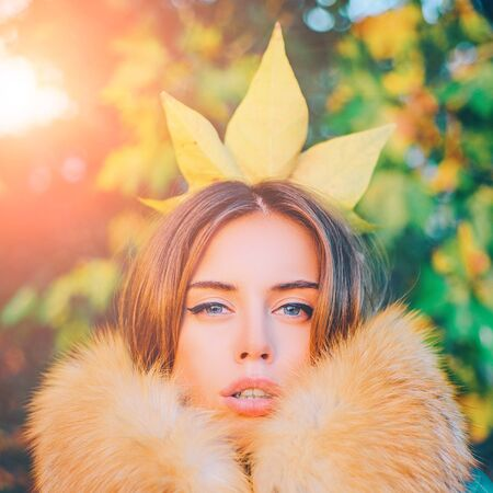 Modern fashion outfit. Gorgeous pretty woman in furry coat fallen leaf on head as crown. Trendy outfit. Her confidence is stunning. Woman feeling as autumn queen