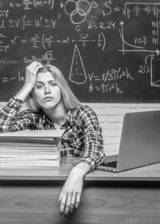 Tired student learning at home. Young college student at hard exam preparation in study hall looking tired and weary. Stock Photo