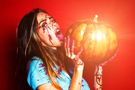 Halloween girl with a bloody Pumpkin. Pretty young blonde woman clothed in dress with pumpkins. Sexy vampire woman with blood on her face. Isolated on red background. 免版税图像 - 128838887