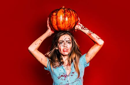 Halloween girl with a Pumpkin. Portrait of a woman with make up blood on her face. Sexy woman wear blue drees with blood. She has pumpkin holds in hands over head. Фото со стока