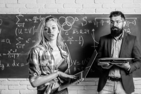 Sexy female student pointing at chalkboard. sexy female student with beautiful breast and teacher in classroom.