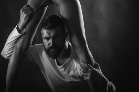 Sexy portrait of handsome brutal bearded male model with beautiful woman legs. Sensual coule and point orgasm. Brutal man takes off her lingerie. Sexy and sensual copy space.