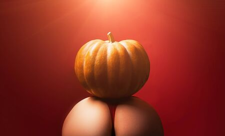 Halloween sexy concept. Big ass for sex celebration. Big ass in intine pose for kamasutra. Hallowen sexy party. Pumpkin on naked big ass. Intime point on woman body. Nightlife and party.