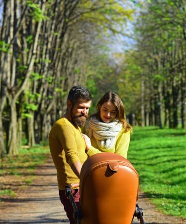 Family relations. Woman and man walk with baby pram in park, happy relations. The right relationship is everything Zdjęcie Seryjne