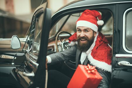 Man in red hat deliver xmas gifts in retro car