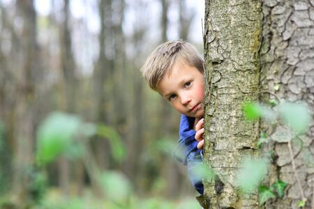 Enjoying my childhood. Little boy have fun in woods. Little boy play hide and seek. Outdoor games is my childhood