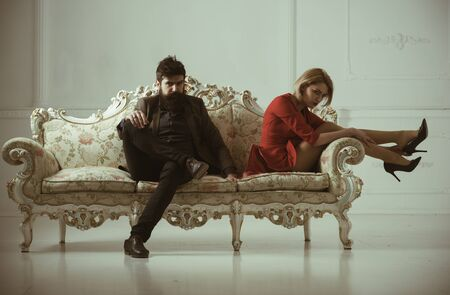 man with woman on sofa. bearded man with girl. man fashion model and sexy lady. business man relaxing with secreatry. confidence and charisma. Zdjęcie Seryjne