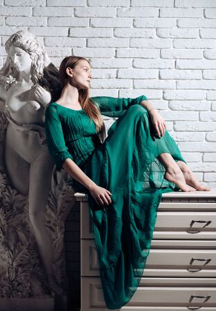 Fashion model in trendy dress. Art and sculpture. Woman artist dream and think at gypsum sculpture at workshop on white brick wall background. Art school education and master class of fine art