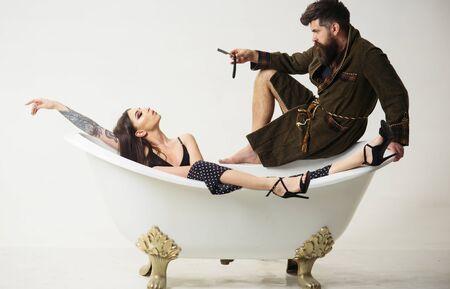 Concetto di rasatura. L'uomo barbuto con il rasoio da barba e la donna si rilassano nella vasca da bagno. Salone di rasatura. Radersi ogni giorno fa crescere la barba Archivio Fotografico