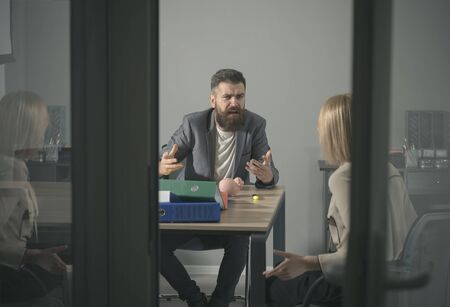 Angry boss shout at accountant in office. Bearded man and woman discuss company budget. Businessman blame financier in money crisis. Business conflict and confrontation. Savings and handout concept