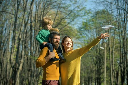 Family launch paper plane in park, traveling concept. Traveling by plane. Lets see the world