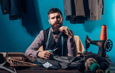 Working on new collection. Bearded man tailor sewing jacket. suit store and fashion showroom. business dress code. Handmade. sewing mechanization. retro modern tailoring workshop. Confident tailor