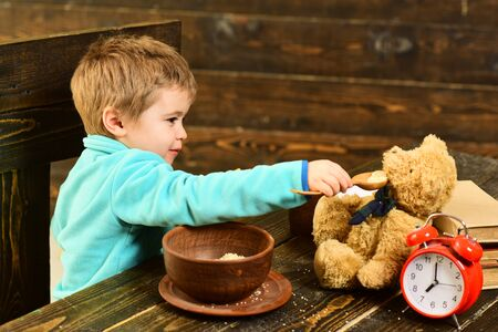 Meal time. Little child and teddy bear have meal together. Boy feed toy friend with healthy meal. Eat a healthy meal to help your body heal