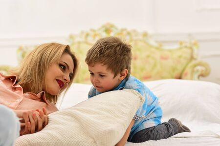 mother with child playing on bed. happy family and childrens day. happy childhood. Care and development. Little boy with mom. little boy play with parents at home. Sincere emotions. Mothers day