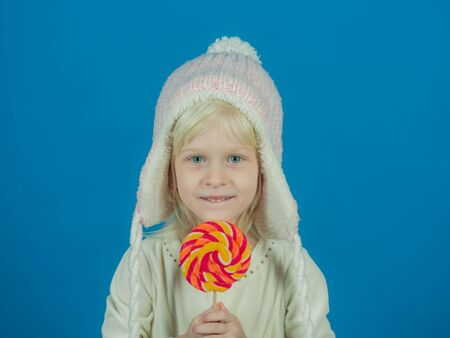 A sweet tooth. Little girl hold lollipop on stick. Little child with sweet lollipop. Happy candy girl. Happy childhood food Stock Photo