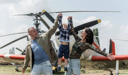 Childhood concept. Kid enjoy happy childhood. Little son in mothers and fathers hands at military air show, childhood. Cute child have childhood dream to be pilot. Love keeps us together
