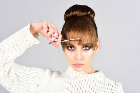 Fashion look and beauty concept. fashion model cut hair with scissors. Imagens