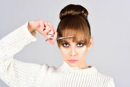 Fashion look and beauty concept. fashion model cut hair with scissors. Zdjęcie Seryjne