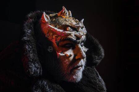 Wizard with thorns on face standing in darkness, nightmare concept. Demon in fur collar on white background. Man with white beard and creative makeup isolated on black background 写真素材 - 128879972